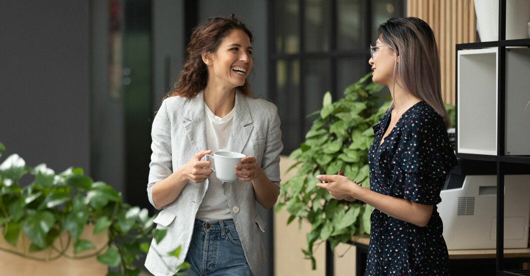 Två kvinnor står bredvid varandra, pratar och skrattar. Den enda har en kopp i handen.