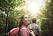 Kvinna som vandrar i skog och motljus
