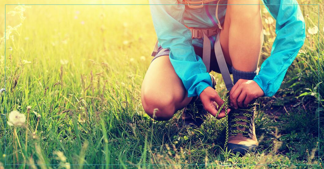 Kvinna som är nybörjare på vandring knyter kängor