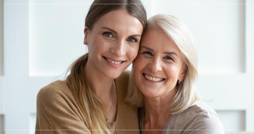 Två kvinnor håller om varandra och ler mot kameran