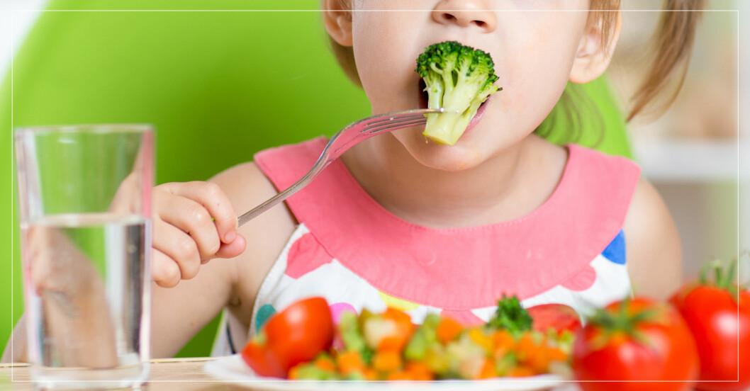 Ett barn som äter grönsaker.