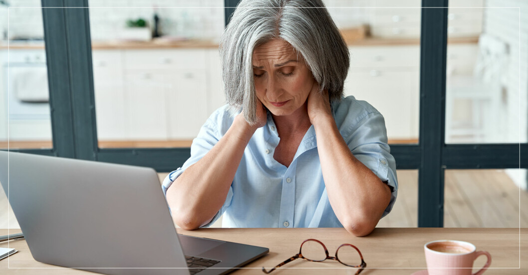 kvinna vid skrivbord med nackvärk pga lång arbetsdag