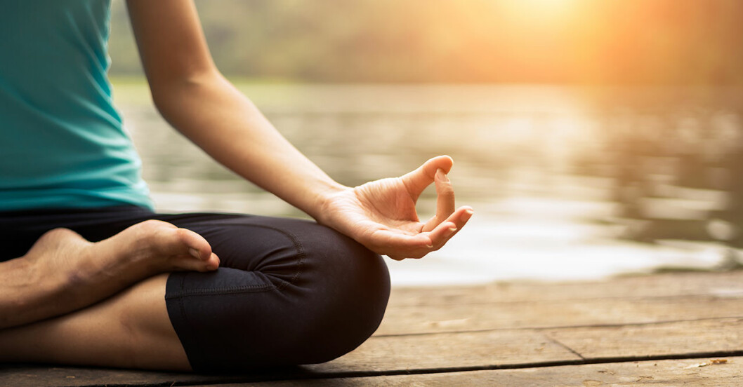 Kvinna sitter i yogapose i solnedgången