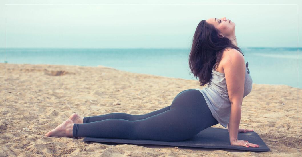 Kvinna gör yoga på en strand.