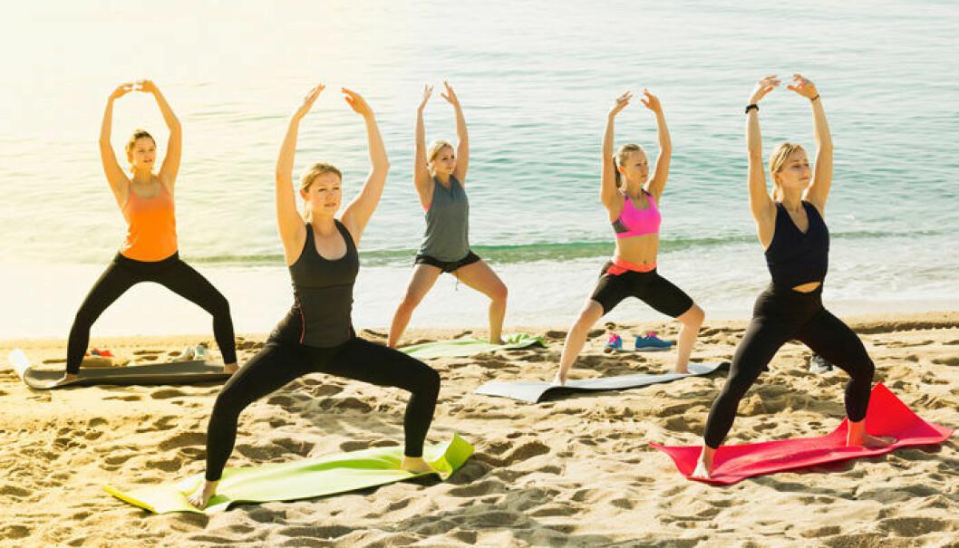 Yoga på stranden vid Spanska solkusten.